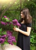 Muchacha del adolescente con las flores de la violeta de la lila Foto de archivo