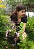 Muchacha del adolescente con las flores en cultivar un huerto del pote Imagen de archivo