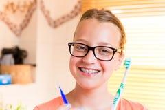Muchacha del adolescente con los apoyos dentales que cepillan sus dientes Imágenes de archivo libres de regalías