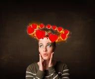 Muchacha del adolescente con los ejemplos del corazón circleing alrededor de su cabeza Fotografía de archivo