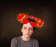 Muchacha del adolescente con los ejemplos del corazón circleing alrededor de su cabeza Imágenes de archivo libres de regalías