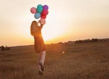 Muchacha del adolescente con los globos en la puesta del sol Fotos de archivo