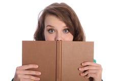 Muchacha del adolescente con los ojos azules que lee un libro Imagenes de archivo