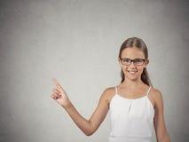 Muchacha del adolescente con los vidrios que señala en el espacio en blanco de la copia Foto de archivo libre de regalías
