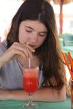 Muchacha del adolescente con sacudida marrón larga de la sandía de la bebida del pelo en café Imagen de archivo