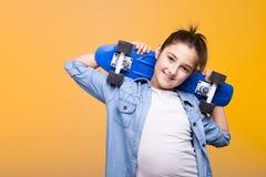 Muchacha del adolescente con un monopatín en sus hombros Imagen de archivo libre de regalías