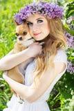 Muchacha del adolescente con una guirnalda de las flores y del perro de la lila Foto de archivo