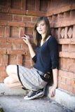 Muchacha del adolescente contra la pared de ladrillo Imágenes de archivo libres de regalías