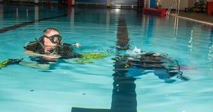 Muchacha del adolescente de la piscina del curso del buceo con escafandra con el instructor en el agua Imagen de archivo