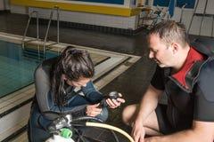 Muchacha del adolescente de la piscina del curso del buceo con escafandra con el instructor en el agua Imagen de archivo libre de regalías