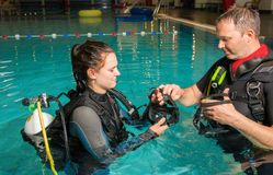 Muchacha del adolescente de la piscina del curso del buceo con escafandra con el instructor en el agua Fotografía de archivo