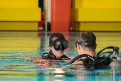 Muchacha del adolescente de la piscina del curso del buceo con escafandra con el instructor en el agua Imágenes de archivo libres de regalías