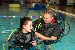 Muchacha del adolescente de la piscina del curso del buceo con escafandra con el instructor en el agua Fotografía de archivo libre de regalías