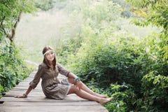 Muchacha del adolescente de la sonrisa en el puente de madera viejo Foto de archivo