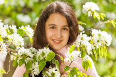 Muchacha del adolescente de Oriente Medio con las flores blancas de la pera Imagenes de archivo
