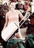 Muchacha del adolescente del pelirrojo que elige el nuevo bolso plástico grande del equipaje Fotografía de archivo
