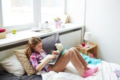 Muchacha del adolescente en cama con el ordenador portátil Fotos de archivo