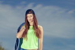 Muchacha del adolescente en casquillo que escucha la música al aire libre Foto de archivo