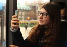 Muchacha del adolescente en el autobús en vidrios de la corrección de la vista Fotos de archivo