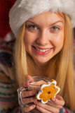 Muchacha del adolescente en el sombrero de santa con la galleta de la Navidad Foto de archivo libre de regalías