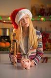Muchacha del adolescente en el sombrero de santa con la hucha Fotos de archivo libres de regalías