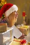 Muchacha del adolescente en el sombrero de santa con la postal de la Navidad Fotografía de archivo libre de regalías