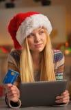 Muchacha del adolescente en el sombrero de santa con la tarjeta de crédito Foto de archivo
