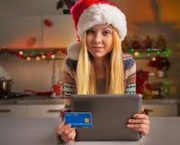 Muchacha del adolescente en el sombrero de santa con la tarjeta de crédito Imagen de archivo libre de regalías