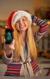 Muchacha del adolescente en el sombrero de santa que hace el selfie Foto de archivo
