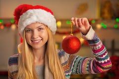 Muchacha del adolescente en el sombrero de santa que muestra la bola de la Navidad Imagen de archivo