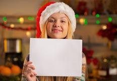 Muchacha del adolescente en el sombrero de santa que muestra la hoja de papel Fotos de archivo