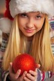 Muchacha del adolescente en el sombrero de santa que sostiene la bola de la Navidad Imagen de archivo