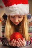 Muchacha del adolescente en el sombrero de santa que sostiene la bola de la Navidad Fotos de archivo