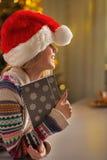 Muchacha del adolescente en el sombrero de santa que sostiene la libreta Foto de archivo