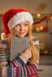 Muchacha del adolescente en el sombrero de santa que sostiene la libreta Fotos de archivo libres de regalías
