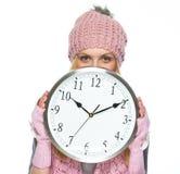 Muchacha del adolescente en el sombrero y la bufanda del invierno que ocultan detrás del reloj Fotografía de archivo libre de regalías
