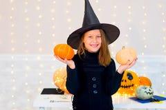 Muchacha del adolescente en el traje de la bruja que presenta con las calabazas Foto de archivo