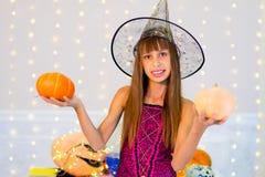 Muchacha del adolescente en el traje de la bruja que presenta con las calabazas Imagenes de archivo