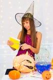 Muchacha del adolescente en el traje de la bruja que presenta con las calabazas Fotos de archivo