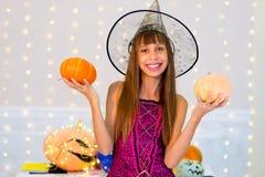 Muchacha del adolescente en el traje de la bruja que presenta con las calabazas Fotografía de archivo