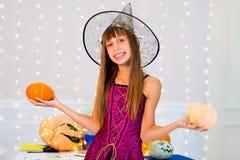 Muchacha del adolescente en el traje de la bruja que presenta con las calabazas Imagen de archivo
