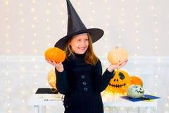 Muchacha del adolescente en el traje de la bruja que presenta con las calabazas Foto de archivo libre de regalías