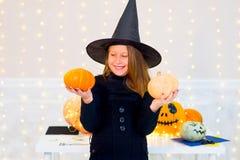 Muchacha del adolescente en el traje de la bruja que presenta con las calabazas Imagen de archivo libre de regalías