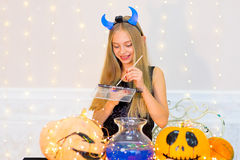Muchacha del adolescente en el traje del demonio que presenta con las calabazas Fotografía de archivo libre de regalías