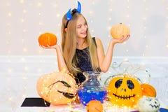 Muchacha del adolescente en el traje del demonio que presenta con las calabazas Imagenes de archivo