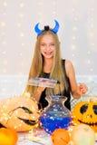Muchacha del adolescente en el traje del demonio que presenta con las calabazas Imagen de archivo