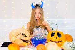 Muchacha del adolescente en el traje del demonio que presenta con las calabazas Imagen de archivo libre de regalías