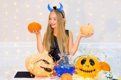 Muchacha del adolescente en el traje del demonio que presenta con las calabazas Foto de archivo libre de regalías