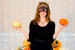 Muchacha del adolescente en el traje del demonio que presenta con las calabazas Fotografía de archivo