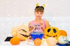 Muchacha del adolescente en el traje del demonio que presenta con las calabazas Fotos de archivo